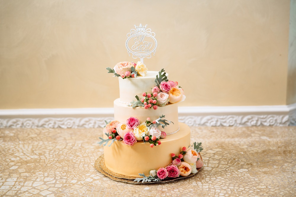 Flowers adorning wedding cake. Accessorise with flowers
