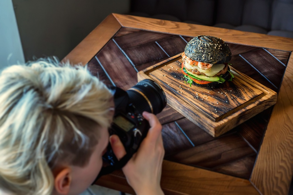 Woman photographing plate with burger