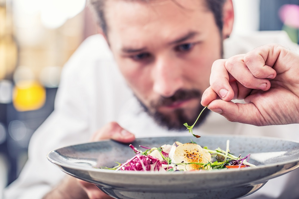 Plating food professionally - chef applies garnish
