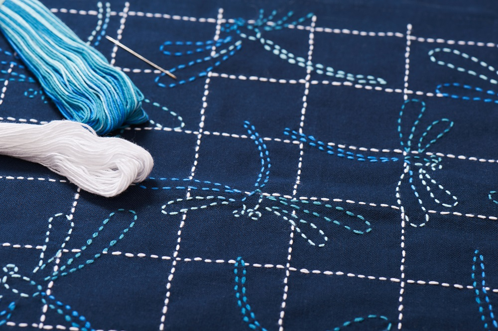 Sashiko embroidery under construction with blue, white and pink threads