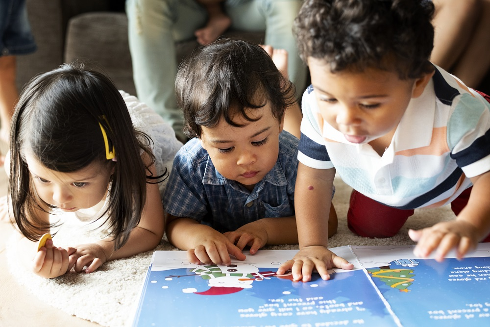 Three children reading from a picture book