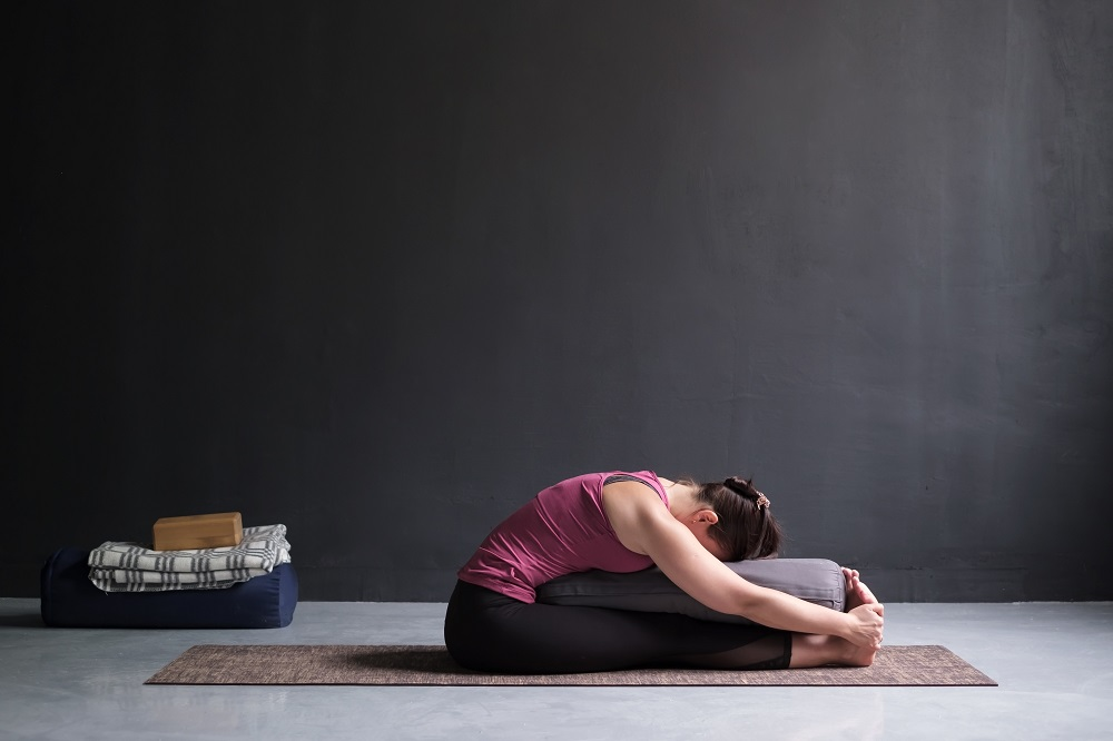 Woman in yin pose resting on bolster
